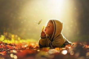 Kind liegt im Wald auf dem Boden und beobachtet einen Schmetterling