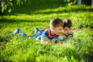zwei Jungs liegen im Gras und schauen durch eine Lupe