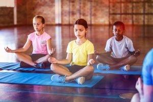 Kinder machen Yoga in einer Gruppe