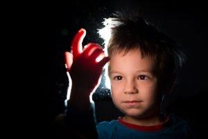Kind wird vor schwarzem Hintergrund angeleuchtet