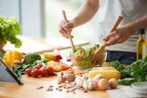 Auf einem Tisch liegen viele Lebensmittel und ein Salat wird zubereitet