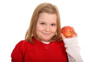 übergewichtiges Kind präsentiert einen Apfel