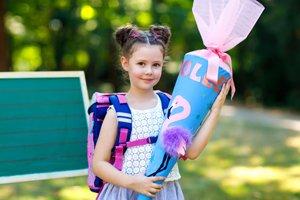kleines Mädchen mit Ranzen und Schultüte
