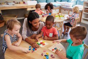 Erzieherin spielt mit Kindern im Kindergarten