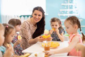 Kinder und Erzieherin essen gemeinsam
