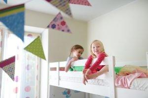 Zwei Mädchen sitzen auf etagenbett