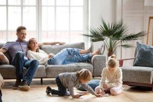 die Eltern sitzen auf dem Sofa, während die Kinder spielen
