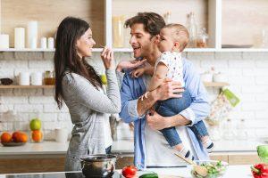 ein junges paar gemeinsam mit ihrem baby beim kochen