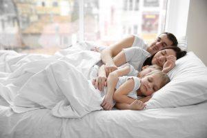 Eine Familie kuschelt gemeinsam im Bett