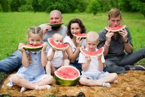 Familie im Park isst Wassermelone