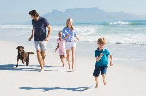 Familie mit Hund am Strand.