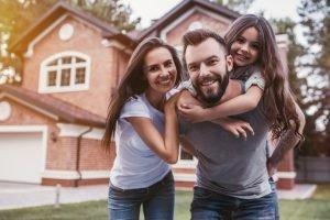 glückliche familie vor einem großen haus