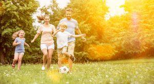 Eltern und Kinder spielen zusammen auf der Wiese