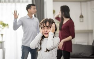 kleines Mädchen weint, während die Eltern im Hintergrund streiten