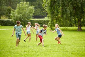 Kinder spielen Fangen auf einer Wiese