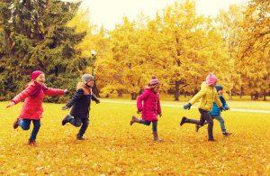 Kinder rennen im Herbst auf einer Wiese herum