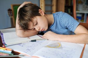 Junge kann sich nicht auf Hausaufgaben konzentrieren