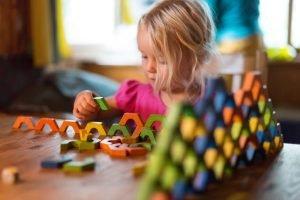 Mädchen spielt mit Bauklötzen am Tisch