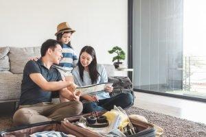 Familie sitzt mit einem Koffer auf dem Boden