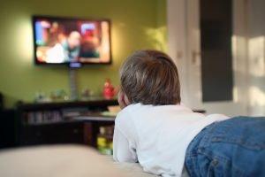ein kind liegt vor dem fernseher