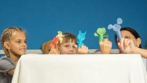 eine familie spielt gemeinsam mit fingerpuppen