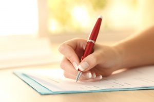 Frau füllt Formulare mit rotem Kugelschreiber aus