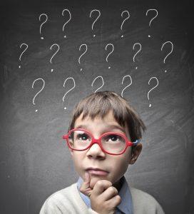 ein kind vor einer tafel mit vielen fragezeichen