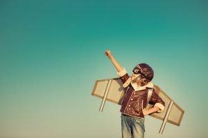 Kind mit Flugzeugflügeln und Fliegerbrille
