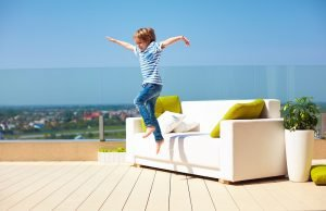 Kind springt vom Sofa