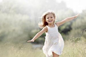 Mädchen in einem weißen Kleid rennt mit ausgebreiteten Armen über eine Wiese