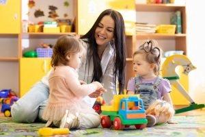 erzieherin spielzt mit freude mit zwei kleinen maedchen im kindergarten