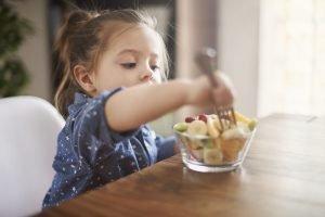 ein kleines Mädchen isst Obst aus einer Schale