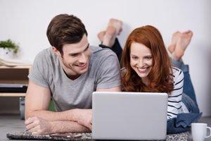 junges Paar guckt auf Laptop und freut sich