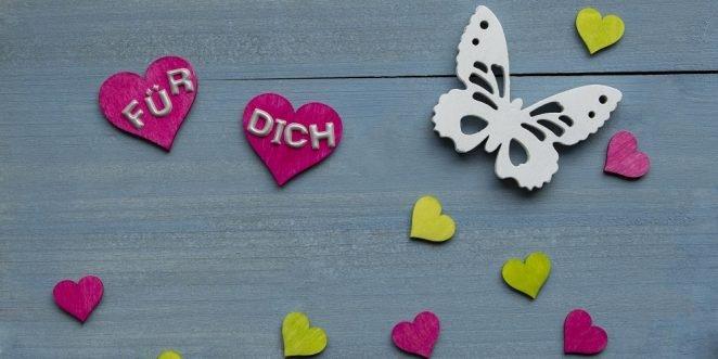 Ausgeschnittene Herzchen und ein Schmetterling auf einer Tischplatte