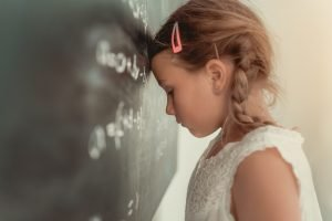 Kind lehnt den Kopf an eine Tafel