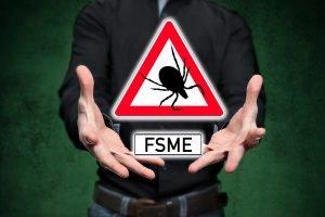 Mann hält ein Warnschild mit einer Zecke und der Aufschrift FSME