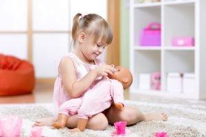 kleines Mädchen umsorgt seine Puppe
