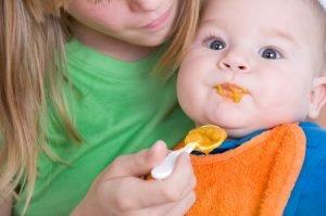 Mutter füttert Babybrei