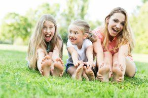 Mutter sitzt mit Töchtern auf einer Wiese