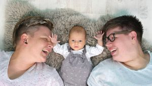 Zwei Frauen liegen mit ihrem Baby zusammen auf einem Fell
