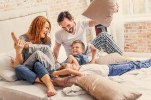 Familie spielt zusammen im Bett