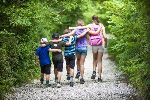 Kinder laufen gemeinsam durch einen Wald