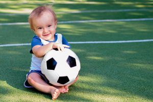 Kind mit einem Fußball in der Hand