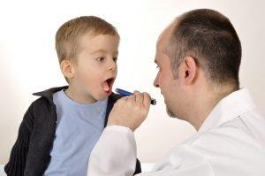 Arzt schaut Kind in den Hals