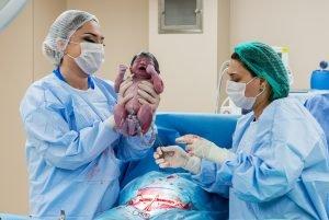 arzte halten ein baby nach der geburt