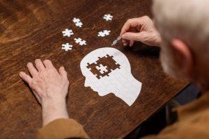 aelterer mann mit puzzleteilen