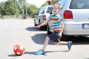 Kind rennt nach Ball auf die Straße