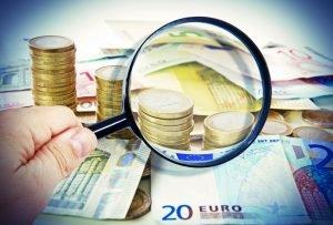 Lupe vor Euro-Münzen und Euro-Scheinen