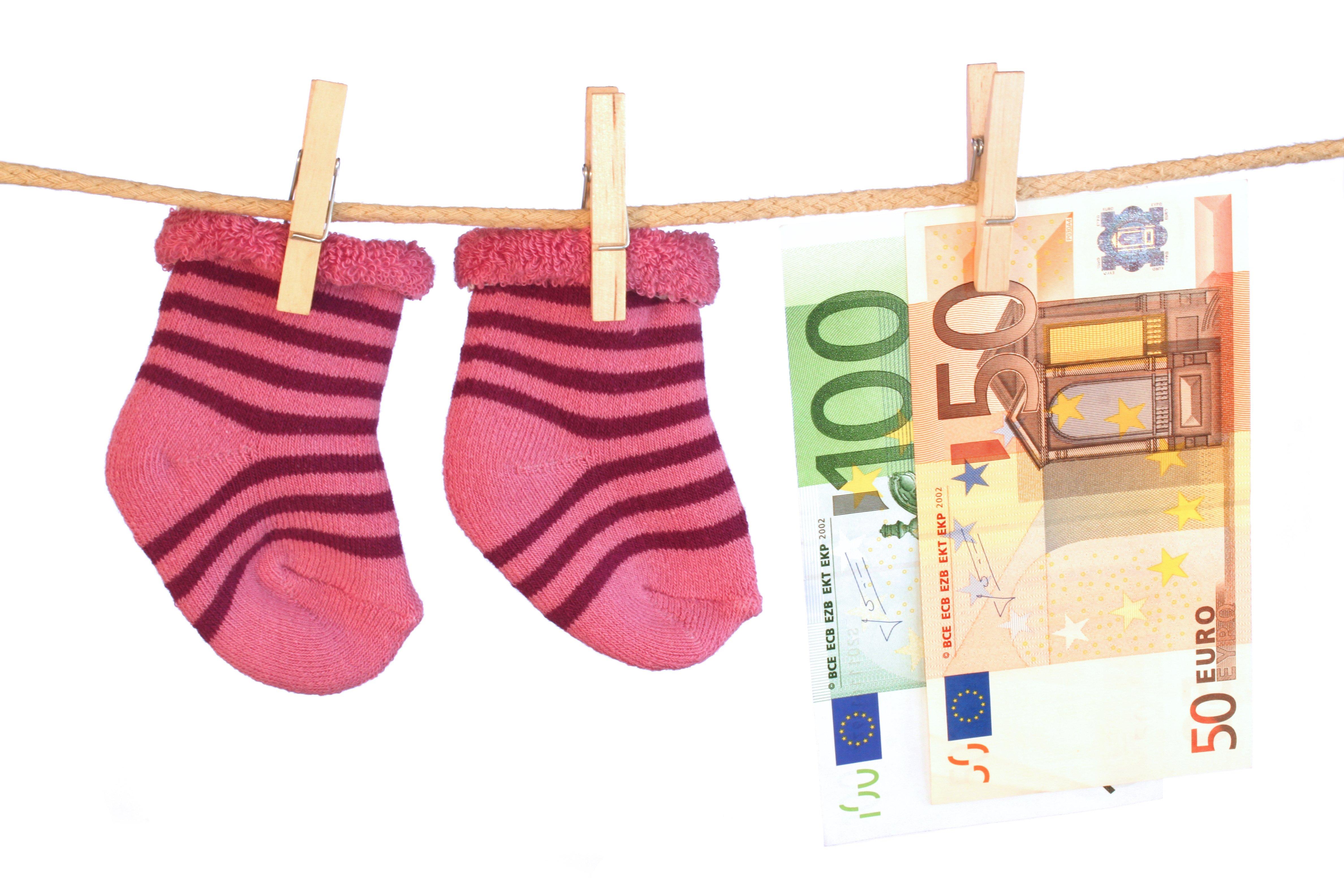 Babysocken und Geld an einer Wäscheleine