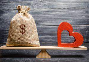 Eine Wippe mit einem Sack voller Geld und einem Herz auf der anderen Seite